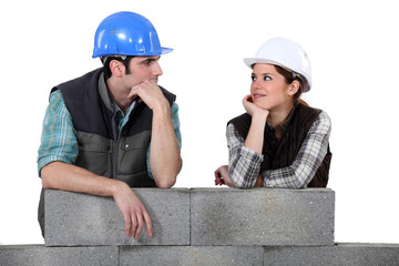 Builders leaning on an unfinished wall
