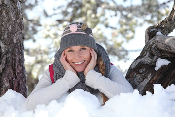 young woman playing with the snow in the park