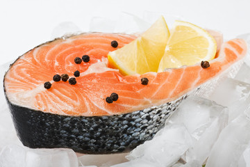 salmon steak with slices of lemon on the ice