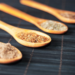 various spices in wooden spoons