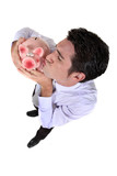 Businessman kissing a piggy bank