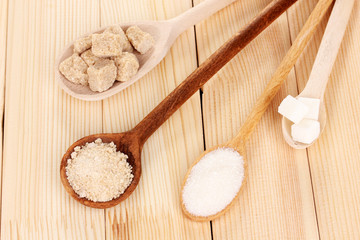 White and brown sugar in spoons on wooden background