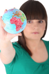 Teenage girl holding miniature globe