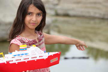 Little girl playing with a toy boat
