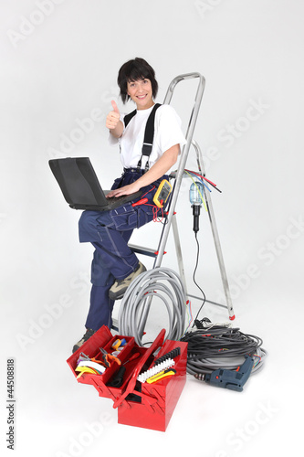 Female electrician surrounded by tools