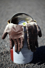 Two used working gloves hanging on empty paint bucket