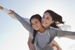 Smiling mother and daughter with arms outstretched on beach