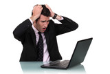 A businessman pissed at his laptop.