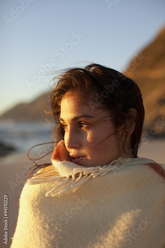 Pensive woman wrapped in blanket on beach