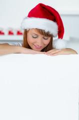 weihnachtsfrau schaut neugierig auf hinweisschild