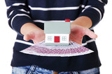 Woman holding euros bills and house model over white.
