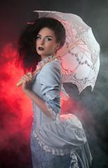 Beautiful Halloween vampire woman aristocrat with lace-parasol