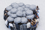 Circle formed by business people with umbrellas