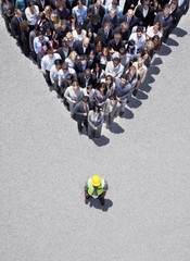 Construction worker at apex of pyramid formed by business people