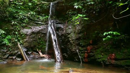 sexy girl with bikini lying down in waterfall river