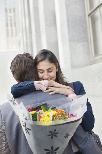 Woman hugging man with flowers behind back