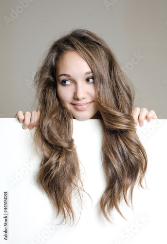 Cute young brunette teen with white banner.