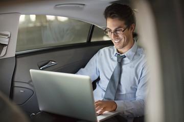 Smiling businessman using laptop in back seat of car at night
