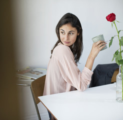 Woman at table drinking coffee and looking back