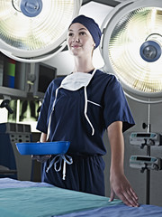 Portrait of confident nurse holding kidney dish under surgical lights