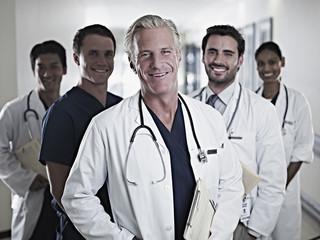 Portrait of smiling doctors and nurse in hospital corridor