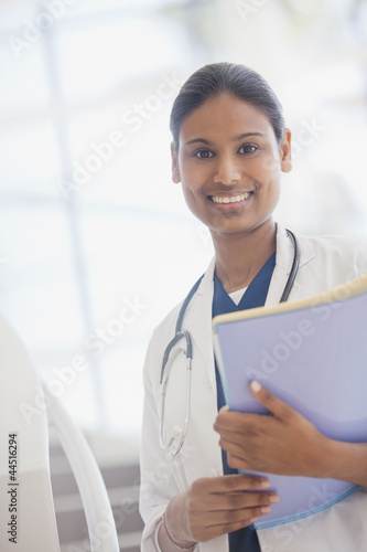 Portrait of smiling doctor holding medical record