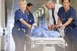 Doctor and nurses wheeling patient in gurney down hospital corridor