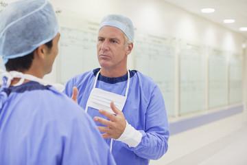 Surgeons talking in hospital corridor