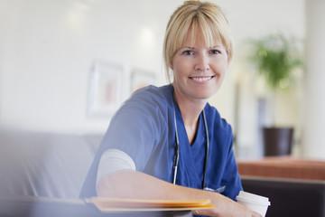 Portrait of smiling nurse drinking coffee in hospital
