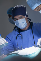 Portrait of serious surgeon holding oxygen mask over patient in operating room