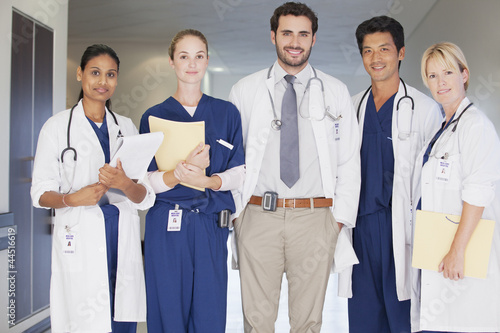 Portrait of smiling doctors and nurse in hospital corridor
