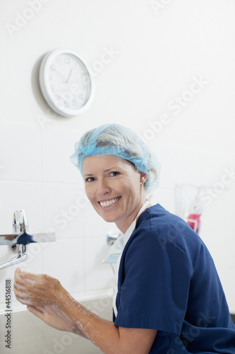 Portrait of smiling nurse washing hands