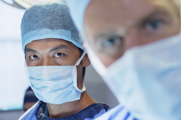 Close up of serious surgeons in surgical masks