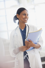 Smiling doctor holding medical records