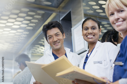 Portrait of smiling doctors and nurse with medical records