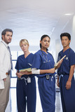 Portrait of serious doctor and nurses in hospital corridor