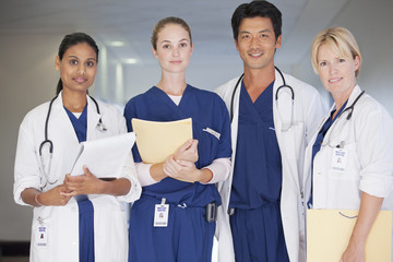 Portrait of smiling doctors and nurse holding medical records in hospital corridor