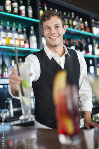 Portrait of smiling bartender holding cocktail