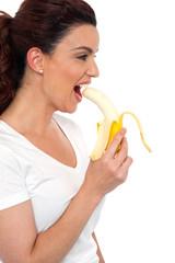 Side view of brunette women eating banana