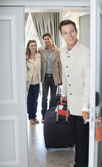 Portrait of bellman opening hotel room door with couple in background