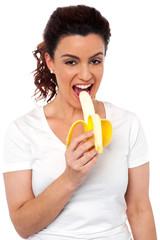 Beautiful young fit girl eating banana