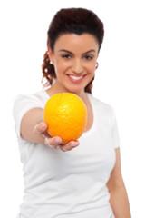 Smiling beautiful woman offering you an orange