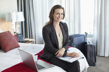 Portrait of smiling businesswoman with paperwork and laptop in hotel room