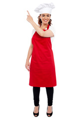 Full length portrait of female chef pointing away