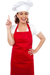 Beautiful smiling female chef indicating upwards