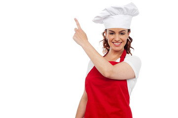 Attractive female chef pointing at copy space