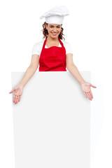 Female chef posing behind blank white billboard