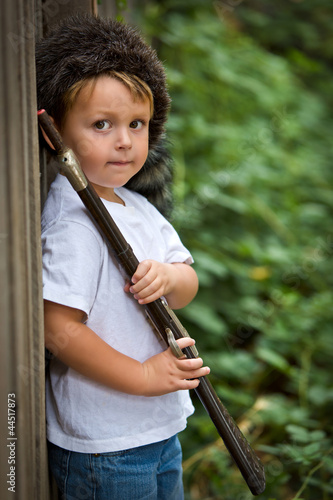 adorable child with toy rifle and coonskin cap