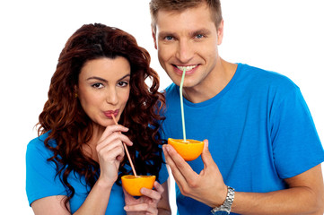 Closeup of couple cuddling and sipping orange juice