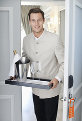 Portrait of waiter in hotel room doorway with tray of champagne and glasses